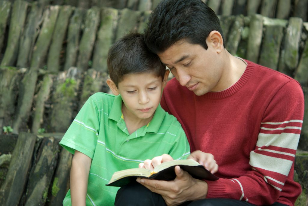 Father and son studying the bible
